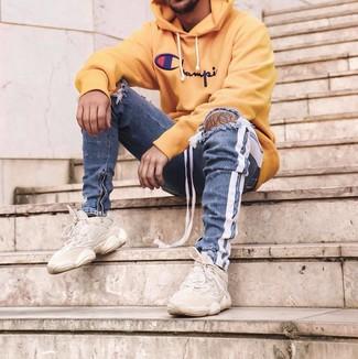 Wie kombinieren: gelber bedruckter Pullover mit einem Kapuze, blaue enge Jeans mit Destroyed-Effekten, hellbeige Sportschuhe