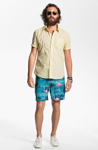 Wie kombinieren: gelbes Kurzarmhemd, türkise bedruckte Shorts, hellbeige niedrige Sneakers