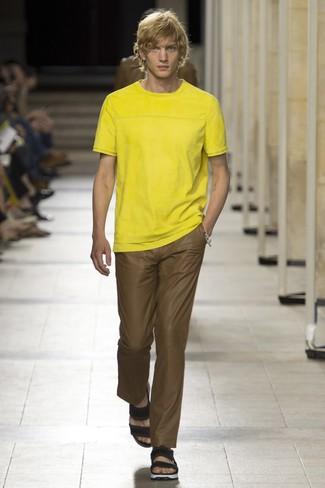Wie kombinieren: gelbes T-Shirt mit einem Rundhalsausschnitt, braune Chinohose, schwarze Ledersandalen