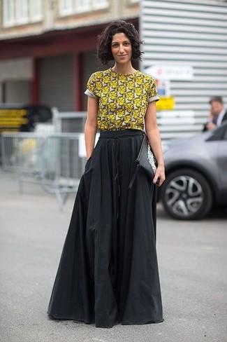 Wie kombinieren: gelbes T-Shirt mit einem Rundhalsausschnitt mit Blumenmuster, schwarzer Falten Maxirock, schwarze und weiße bedruckte Leder Clutch