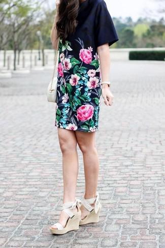 Wie kombinieren: schwarzes gerade geschnittenes Kleid mit Blumenmuster, hellbeige elastische Keilsandaletten, weiße Leder Umhängetasche, goldene Uhr