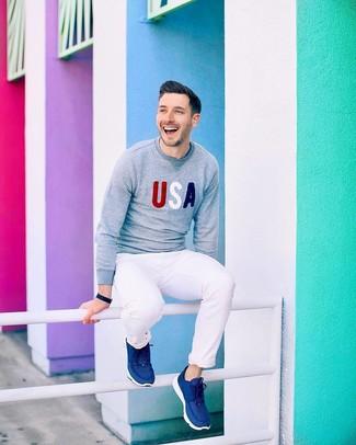 Wie kombinieren: grauer bedruckter Pullover mit einem Rundhalsausschnitt, weiße Chinohose, dunkelblaue Sportschuhe