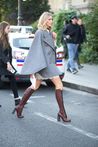 grauer Cape Mantel, weißes gerade geschnittenes Kleid aus Spitze, dunkelrote kniehohe Stiefel aus Leder für Damen