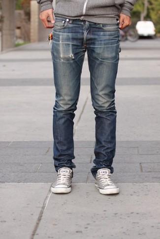 Wie kombinieren: grauer Pullover mit einem Kapuze, dunkelblaue Jeans, graue Segeltuch niedrige Sneakers