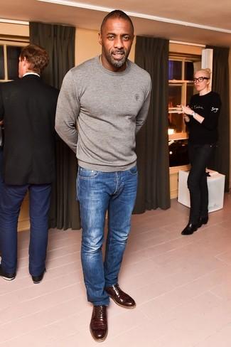 Idris Elba trägt grauer Pullover mit einem Rundhalsausschnitt, blaue Jeans, dunkelbraune Leder Brogues
