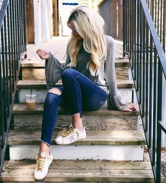 Grauen Pullover mit einem Rundhalsausschnitt kombinieren – 49 Lässige Damen Outfits: Die Paarung aus einem grauen Pullover mit einem Rundhalsausschnitt und dunkelblauen engen Jeans mit Destroyed-Effekten ist eine gute Option füreinen entspannten Alltags-Look. Weiße Leder niedrige Sneakers sind eine kluge Wahl, um dieses Outfit zu vervollständigen.
