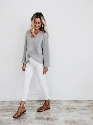 Wie kombinieren: grauer Pullover mit einem V-Ausschnitt, weiße enge Jeans, beige Leder Stiefeletten mit Ausschnitten
