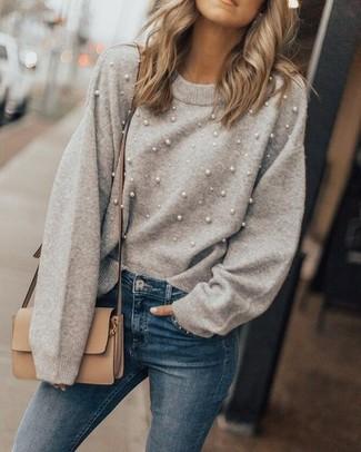 Wie kombinieren: grauer verzierter Pullover mit einem Rundhalsausschnitt, blaue enge Jeans, beige Leder Umhängetasche