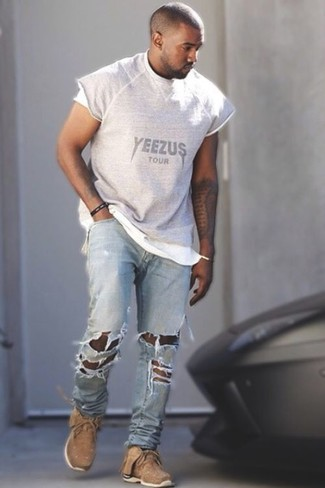 Kanye West trägt Graues bedrucktes T-Shirt mit Rundhalsausschnitt, Hellblaue Jeans mit Destroyed-Effekten, Beige Sportschuhe