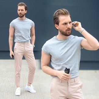 Wie kombinieren: graues T-Shirt mit einem Rundhalsausschnitt, rosa Chinohose, weiße niedrige Sneakers