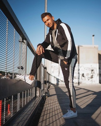 Wie kombinieren: graues T-Shirt mit einem Rundhalsausschnitt, schwarzer und weißer Trainingsanzug, weiße niedrige Sneakers