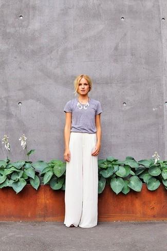 Wie kombinieren: graues T-Shirt mit einem Rundhalsausschnitt, weiße weite Hose aus Seide, weiße verzierte Halskette
