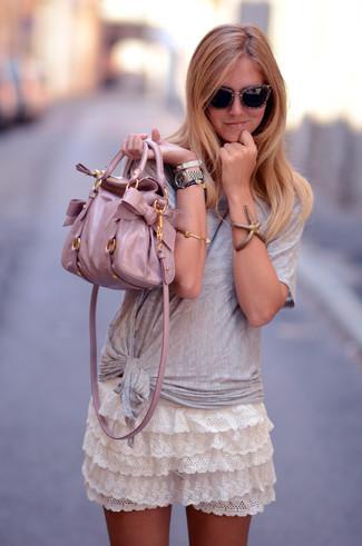 Wie kombinieren: graues T-Shirt mit einem Rundhalsausschnitt, weißer Spitze Minirock mit Rüschen, rosa Shopper Tasche aus Leder