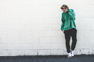 Wie kombinieren: grüner Strick Oversize Pullover, schwarze Jogginghose, weiße und schwarze Sportschuhe