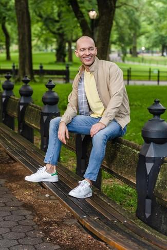 Wie kombinieren: beige Harrington-Jacke, gelbes T-Shirt mit einem Rundhalsausschnitt, blaue Jeans, weiße Leder niedrige Sneakers