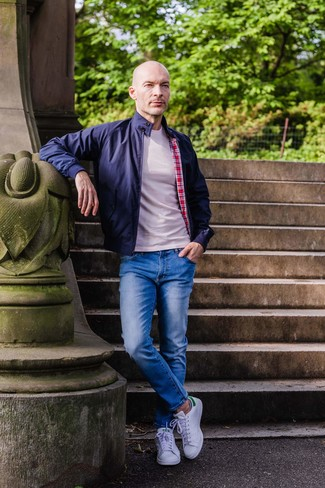 Wie kombinieren: dunkelblaue Harrington-Jacke, hellbeige T-Shirt mit einem Rundhalsausschnitt, blaue Jeans, weiße Leder niedrige Sneakers