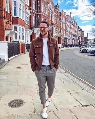 Herren Outfits 2020: Kombinieren Sie eine braune Wollharrington-jacke mit einer grauen Chinohose für ein bequemes Outfit, das außerdem gut zusammen passt. Fühlen Sie sich mutig? Vervollständigen Sie Ihr Outfit mit weißen bedruckten Leder niedrigen Sneakers.