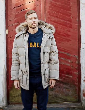 Wie kombinieren: hellbeige Daunenmantel, dunkelblaues bedrucktes Sweatshirt, dunkelblaue Jeans