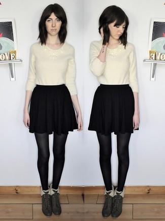 Wie kombinieren: hellbeige flauschiger Pullover mit einem Rundhalsausschnitt, schwarzer Skaterrock, dunkelgrüne Wildleder Stiefeletten