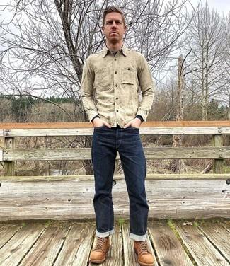 Herren Outfits 2020: Tragen Sie ein hellbeige Langarmhemd und dunkelblauen Jeans, um einen lockeren, aber dennoch stylischen Look zu erhalten. Eine rotbraune Wildlederfreizeitstiefel bringen Eleganz zu einem ansonsten schlichten Look.