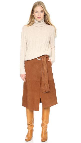 Wie kombinieren: hellbeige Rollkragenpullover, brauner Midirock aus Wildleder, beige kniehohe Stiefel aus Leder