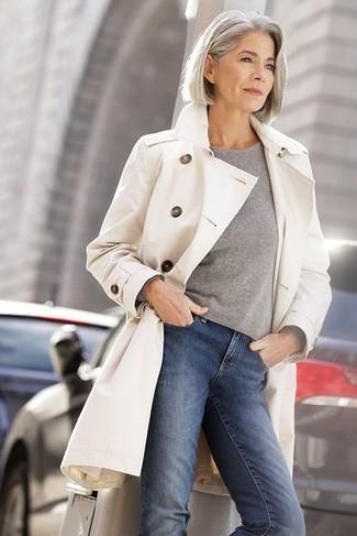 hellbeige Trenchcoat, grauer Pullover mit einem Rundhalsausschnitt, blaue enge Jeans für Damen