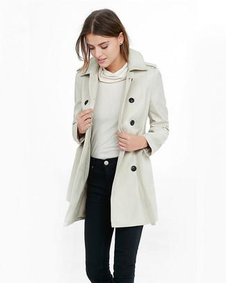 Wie kombinieren: hellbeige Trenchcoat, weißer Pullover mit einer weiten Rollkragen, schwarze enge Jeans