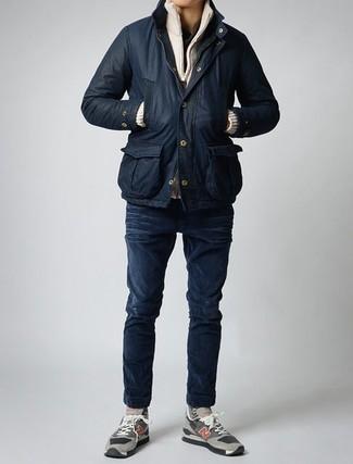 Wie kombinieren: schwarze Jacke mit einer Kentkragen und Knöpfen, hellbeige Pullover mit einem Reißverschluß, schwarzes T-shirt mit einer Knopfleiste, dunkelblaue enge Jeans