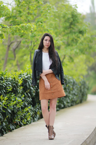Eine Schwarze Lederjacke und ein Beige Rock mit Knöpfen sind das Outfit Ihrer Wahl für faule Tage. Machen Sie Ihr Outfit mit Braunen Leder Stiefeletten mit Schlangenmuster eleganter.