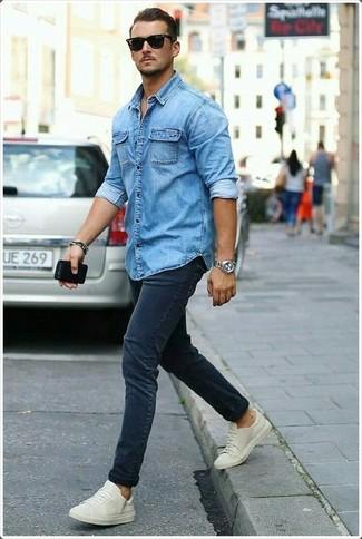 Wie kombinieren: blaues Jeanshemd, dunkelblaue enge Jeans, hellbeige niedrige Sneakers, schwarze Sonnenbrille