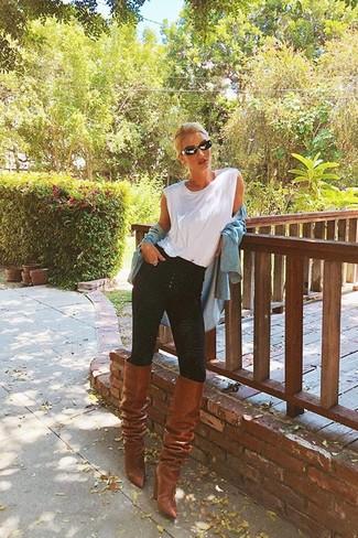 Wie kombinieren: hellblaues Jeanshemd, weißes Trägershirt, schwarze enge Jeans, braune kniehohe Stiefel aus Leder