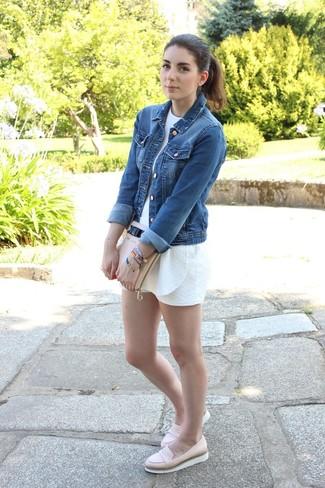 Wie kombinieren: blaue Jeansjacke, weißer kurzer Jumpsuit, hellbeige Leder Slipper, hellbeige Leder Clutch
