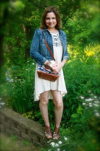 Wie kombinieren: blaue Jeansjacke, hellbeige bedrucktes schwingendes Kleid, dunkelbraune Römersandalen aus Leder, mehrfarbiges Armband