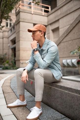 Wie kombinieren: hellblaue Jeansjacke, hellbeige Chinohose, weiße Leder niedrige Sneakers, orange Baseballkappe