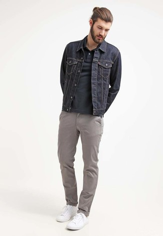 Wie kombinieren: dunkelblaue Jeansjacke, schwarzes Polohemd, graue Chinohose, weiße niedrige Sneakers