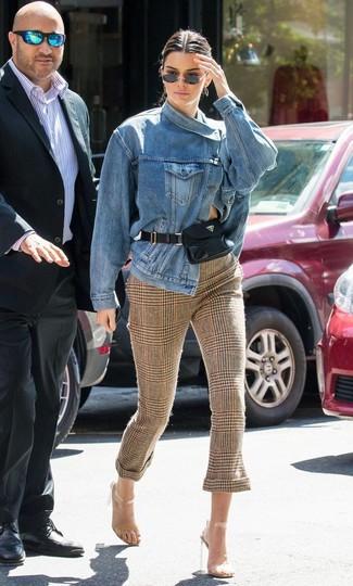 Wie kombinieren: blaue Jeansjacke, braune enge Hose mit Schottenmuster, transparente Gummi Sandaletten, schwarze Leder Bauchtasche