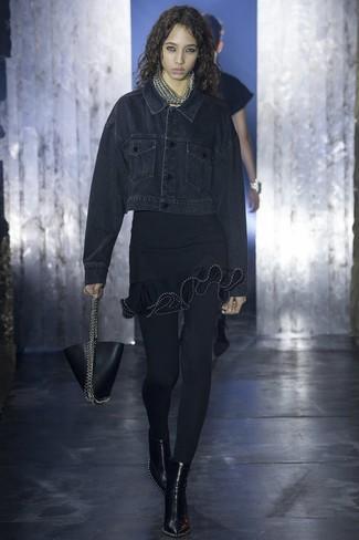 schwarze Jeansjacke, schwarzes figurbetontes Kleid mit Rüschen, schwarze Leder Stiefeletten, schwarze Lederhandtasche für Damen