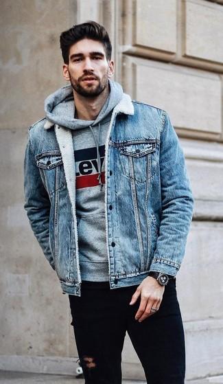 Wie kombinieren: hellblaue Jeansjacke, grauer bedruckter Pullover mit einem Kapuze, schwarze enge Jeans mit Destroyed-Effekten, schwarze Lederuhr