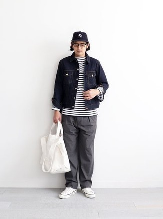 Herren Outfits 2020: Kombinieren Sie eine dunkelblaue Jeansjacke mit einer grauen Chinohose für ein Alltagsoutfit, das Charakter und Persönlichkeit ausstrahlt. Suchen Sie nach leichtem Schuhwerk? Wählen Sie weißen Segeltuch niedrige Sneakers für den Tag.