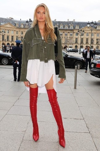 Wie kombinieren: olivgrüne Jeansjacke, weißes Shirtkleid, rote Overknee Stiefel aus Leder, schwarze Leder Umhängetasche