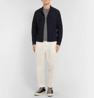 Wie kombinieren: schwarze Jeansjacke, weißes und schwarzes horizontal gestreiftes Langarmshirt, weiße Anzughose, schwarze und weiße hohe Sneakers aus Segeltuch
