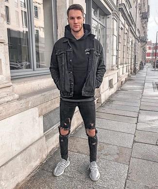 Wie kombinieren: schwarze Jeansjacke, schwarzer Pullover mit einem Kapuze, schwarze enge Jeans mit Destroyed-Effekten, graue Sportschuhe