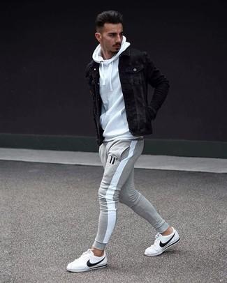 Wie kombinieren: schwarze Jeansjacke, weißer Pullover mit einem Kapuze, graue Jogginghose, weiße Leder niedrige Sneakers
