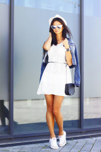 Wie kombinieren: blaue Jeansjacke, weißes Skaterkleid, weiße Segeltuch niedrige Sneakers, schwarze Leder Umhängetasche