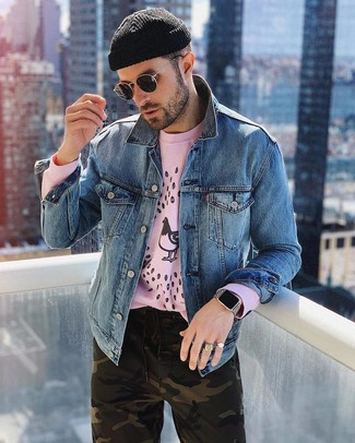 Wie kombinieren: blaue Jeansjacke, rosa bedrucktes Sweatshirt, olivgrüne Camouflage Chinohose, schwarze Mütze