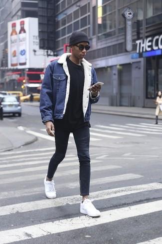 Wie kombinieren: blaue Jeansjacke, schwarzes Sweatshirt, dunkelblaue enge Jeans, weiße Leder niedrige Sneakers