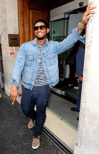 Usher trägt hellblaue Jeansjacke, weißes und dunkelblaues horizontal gestreiftes T-Shirt mit einem Rundhalsausschnitt, dunkelblaue Cargohose, beige niedrige Sneakers mit Leopardenmuster