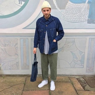 Wie kombinieren: dunkelblaue Jeansjacke, graues T-Shirt mit einem Rundhalsausschnitt, olivgrüne Chinohose, weiße niedrige Sneakers