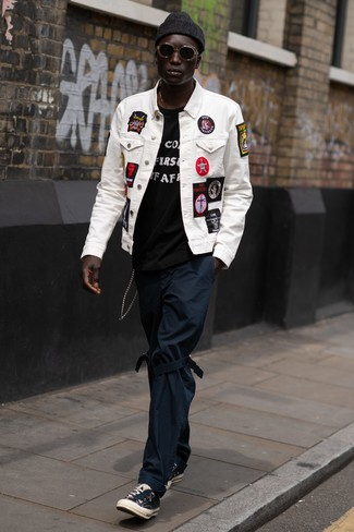 Wie kombinieren: weiße bestickte Jeansjacke, schwarzes und weißes bedrucktes T-Shirt mit einem Rundhalsausschnitt, dunkelblaue Chinohose, schwarze Segeltuch niedrige Sneakers