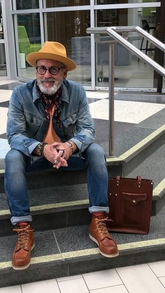 Wie kombinieren: blaue Jeansjacke, orange T-Shirt mit einem Rundhalsausschnitt, blaue enge Jeans, braune Lederarbeitsstiefel